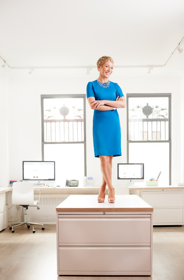 Barbara Corcoran stands on desk in blue dress | Editorial